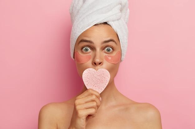 Mulher adulta estupefata cuida da pele delicada sob os olhos, cobre a boca com uma esponja cosmética, adesivos de hidrogel sob os olhos e fica nua contra a parede rosa. conceito de beleza
