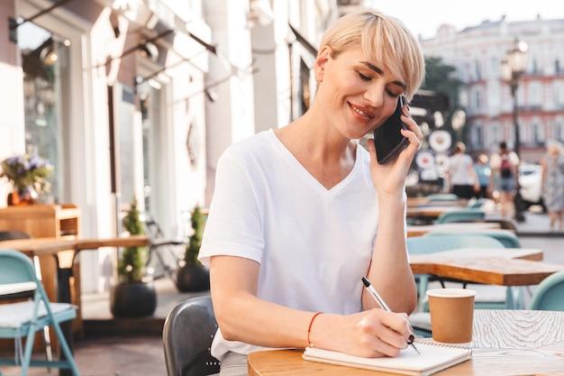 Mulher adulta europeia vestindo uma camiseta branca sentada em um café de verão ao ar livre, enquanto escreve no caderno e fala no smartphone