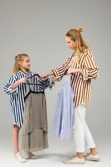 Mulher adulta experiente e atenciosa, propondo outro vestido para sua irmã mais nova, enquanto experimenta diferentes variantes