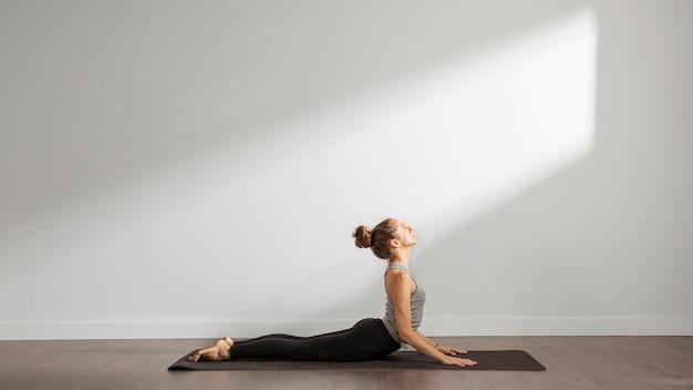 Mulher adulta fazendo ioga em casa