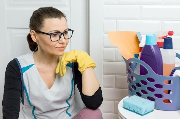 Mulher adulta fazendo limpeza com detergentes