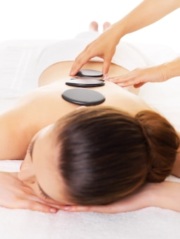 Mulher adulta fazendo massagem com pedras quentes no salão spa. conceito de tratamento de beleza.
