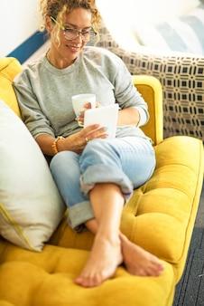 Mulher adulta feliz aproveite o tempo de relaxamento em casa lendo um livro digital em um dispositivo moderno, sentada confortável no sofá - vista de cima do retrato de uma jovem deitada no sofá para fazer uma pausa