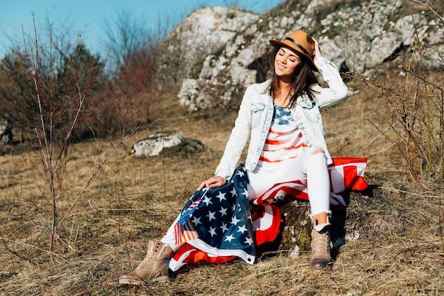 Mulher adulta feliz com bandeira segurando o chapéu