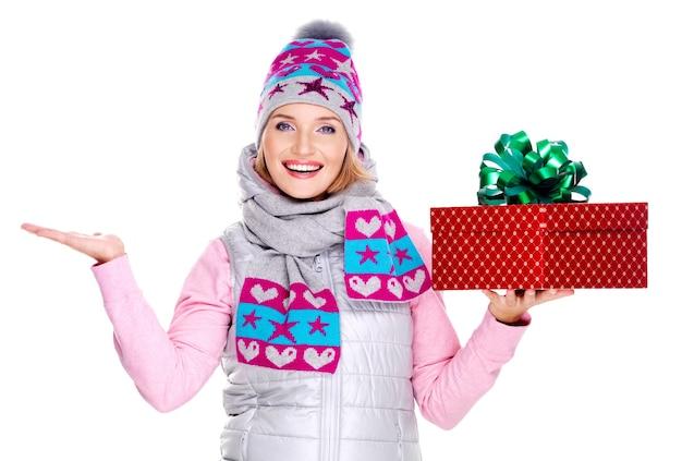 Mulher adulta feliz com um presente e um espaço de cópia em outra mão levantada isolado no branco