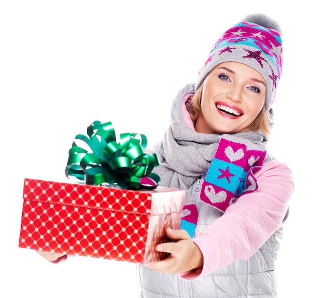 Mulher adulta feliz dando um presente de natal em um casaco de inverno isolado no branco