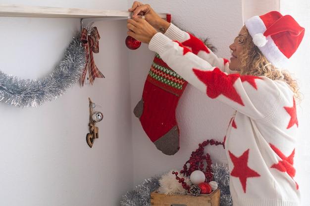 Mulher adulta feliz decorando a casa com bolas e meias de natal - férias de inverno, temporada de dezembro. véspera de ano novo e celebração de natal pessoas