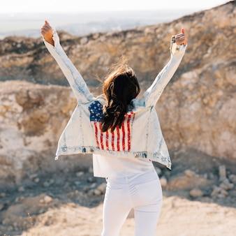 Mulher adulta feliz levantando as mãos na montanha