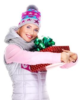 Mulher adulta feliz segurando a caixa vermelha de presente de natal em um casaco de inverno isolado no branco