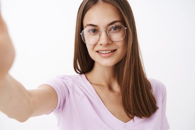 Mulher adulta inteligente, atraente e confiante, em óculos elegantes, puxando a mão e sorrindo enquanto tira uma selfie ou grava uma mensagem de vídeo com o novo smartphone