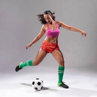 Mulher adulta, jogando futebol