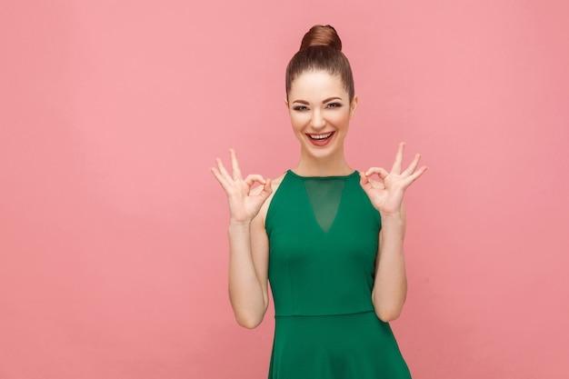 Mulher adulta jovem atraente mostrando sinal de ok. conceito de emoção e sentimentos de expressão. foto de estúdio, isolada em fundo rosa