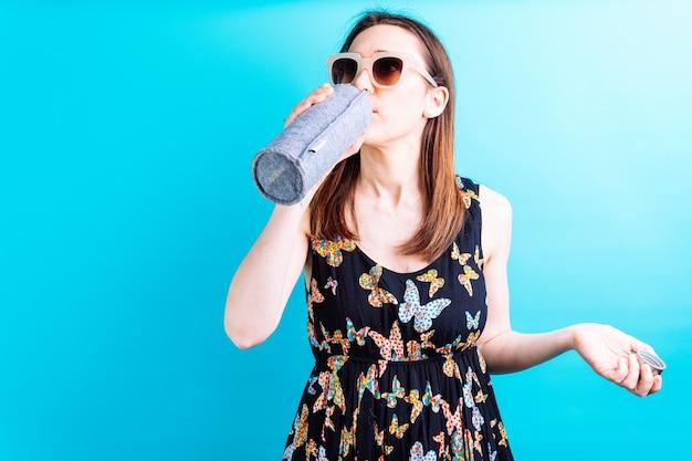 Mulher adulta jovem bonita na jaqueta amarela e água potável de fundo azul com óculos de sol. chegada do conceito de verão com calor. precisa se hidratar