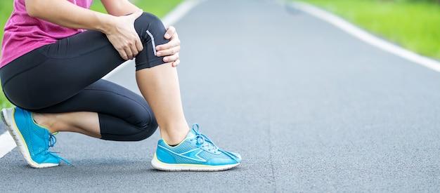 Mulher adulta jovem com dores musculares durante a corrida.