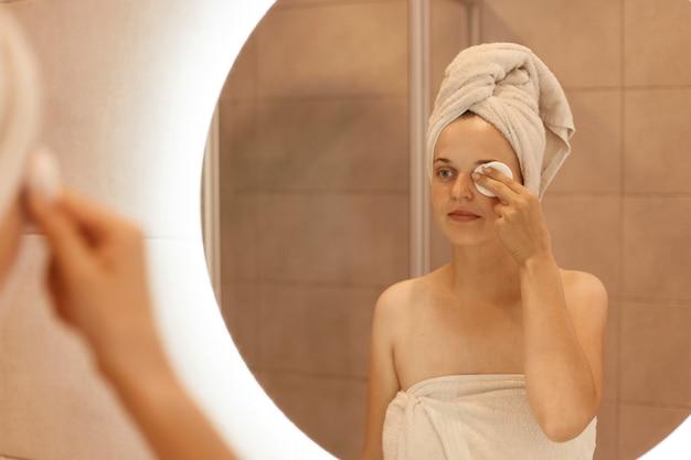 Mulher adulta jovem e atraente caucasiana na toalha no cabelo, olhando no espelho e limpando o rosto com uma almofada de algodão, de pé no banheiro depois de tomar banho.