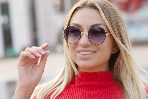 Mulher adulta jovem feliz sorrindo com dentes ao ar livre e andando na rua da cidade. retrato de uma jovem linda rindo