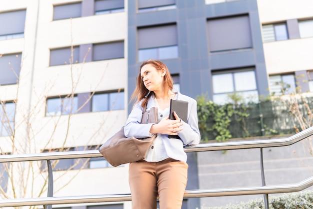 Mulher adulta jovem linda empresária segurando o tablet de negócios. conceito de mulher de negócios bem-sucedido. copie o espaço. conceito de negócio imobiliário