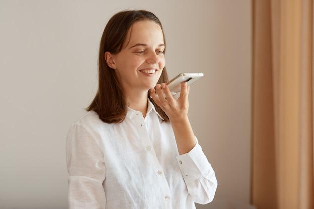 Mulher adulta jovem satisfeita positiva vestindo camisa de algodão branco, segurando o telefone celular nas mãos e gravando mensagem de voz, tendo uma expressão facial positiva.