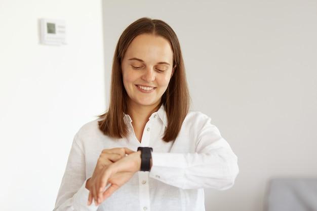Mulher adulta jovem sorridente com aparência agradável, vestindo camisa branca estilo casual em pé usando smartwatch, olhando e tocando a tela sensível ao toque, expressando felicidade, tecnologia moderna.