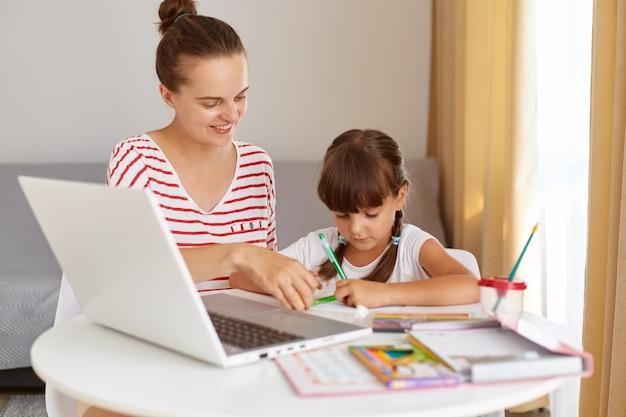 Mulher adulta jovem sorridente, vestindo roupas casuais listradas, ajudando a filha a fazer o dever de casa, educação à distância durante a quarentena, aula online.