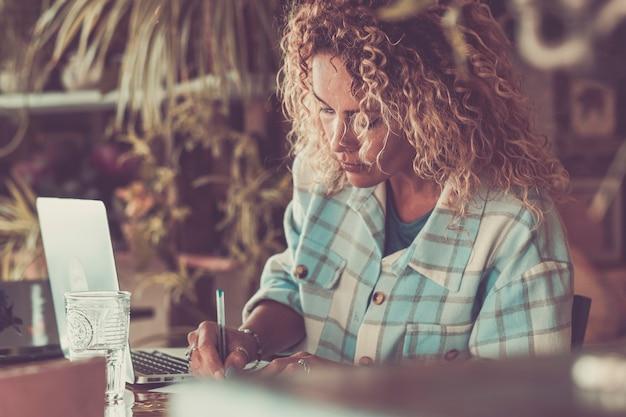 Mulher adulta jovem trabalhando na área de trabalho em uma atividade de trabalho inteligente - mulher de negócios jovem hippie com computador laptop trabalhando em casa - retrato de mulher em cores marrons estilizadas
