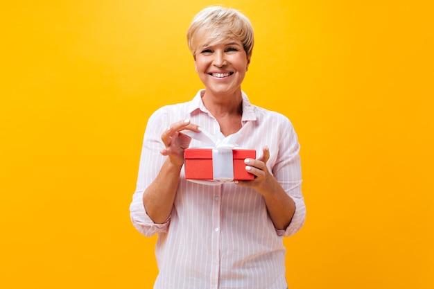 Mulher adulta legal sorri e segura uma caixa de presente em fundo laranja