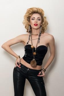 Mulher adulta loira sexy com espartilho preto e calças de couro posando sobre fundo branco