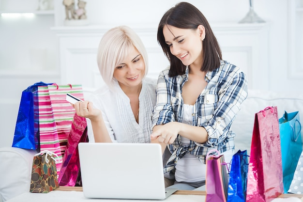 Mulher adulta meada e sua filha fazendo compras on-line em casa. família feliz comprando bens de internet em casa. mulheres que encomendam online.