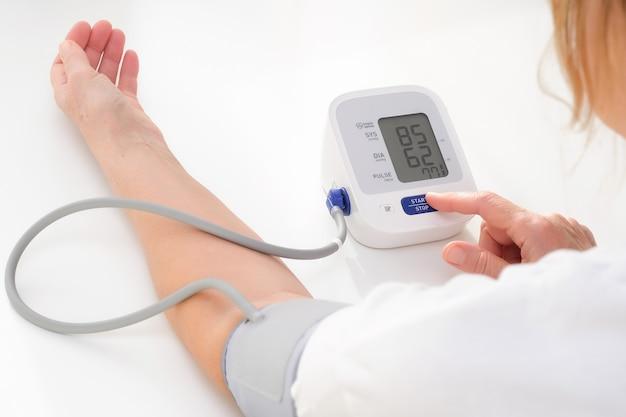 Mulher adulta mede a pressão arterial, fundo branco. hipotensão arterial.