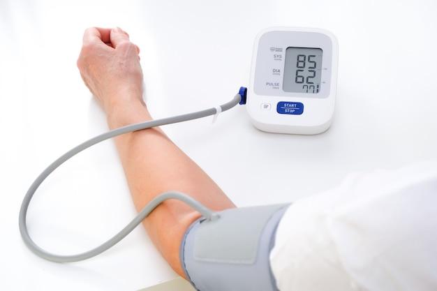 Mulher adulta mede a pressão arterial