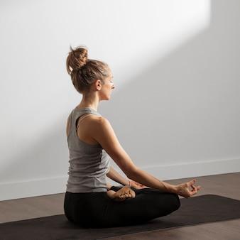 Mulher adulta meditando em casa