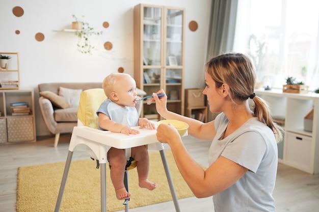 Mulher adulta moderna alimentando seu filho bebê alegre com mingau na sala de estar em casa