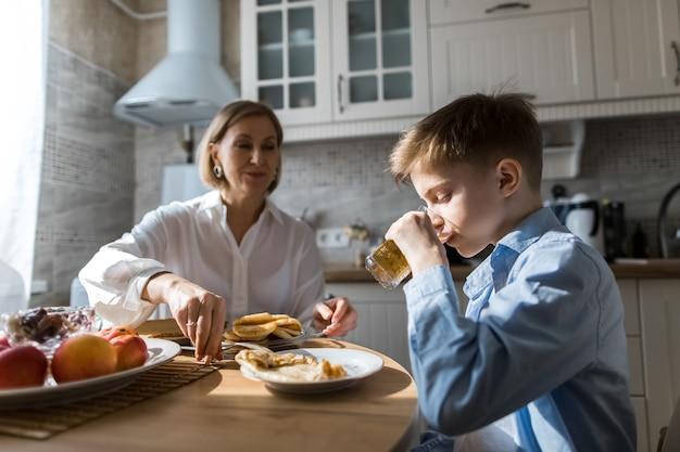 Mulher adulta na cozinha trata uma criança com suco.