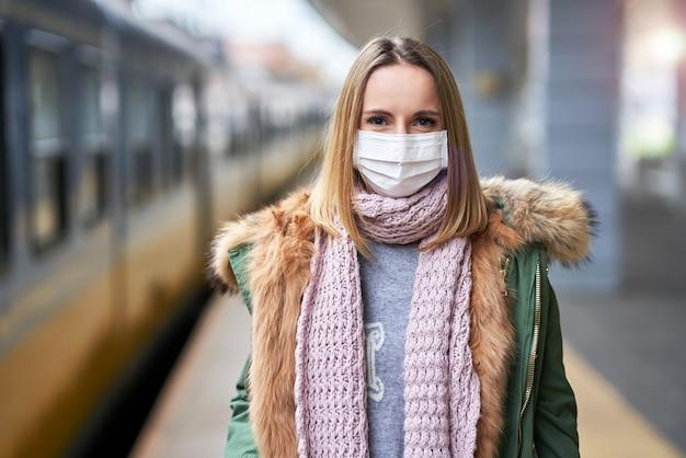 Mulher adulta na estação de trem usando máscaras devido às restrições covid-19