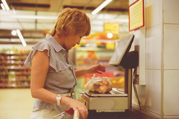 Mulher adulta na mercearia fazendo compras de comida