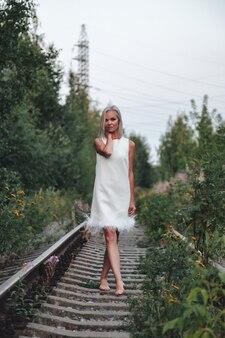 Mulher adulta na natureza caminhando na floresta de verão na ferrovia do crepúsculo. senhora sonhadora em vestido de caminhada à noite na ferrovia. emoção positiva feminina nos trilhos ao amanhecer