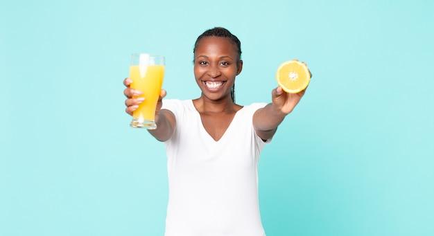 Mulher adulta negra afro-americana. conceito de suco de laranja