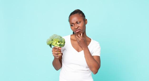 Mulher adulta negra afro-americana segurando um brócolis Foto Premium