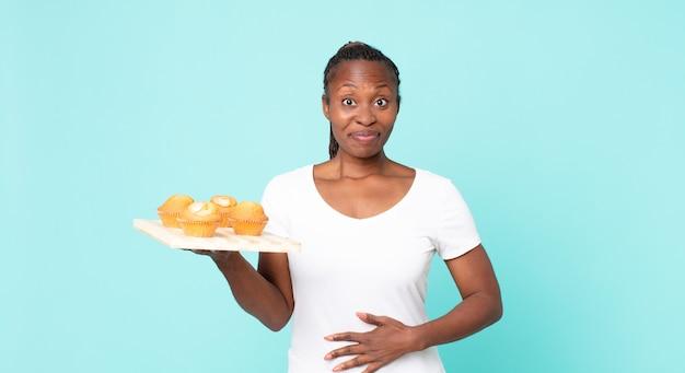 Mulher adulta negra afro-americana segurando uma bandeja de muffins
