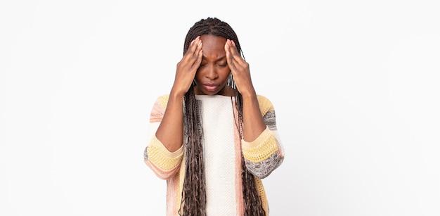 Mulher adulta negra parecendo estressada e frustrada, trabalhando sob pressão, com dor de cabeça e preocupada com problemas