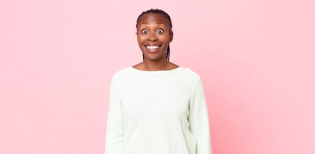 Mulher adulta negra parecendo feliz e agradavelmente surpresa, animada com uma expressão de fascínio e choque