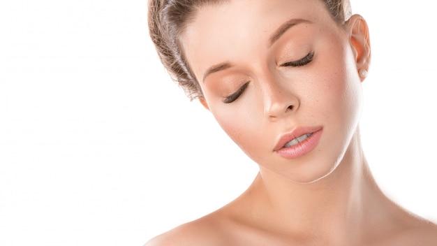 Mulher adulta nova com cara bonita e olhos fechados, pele saudável - isolada no branco. conceito de cuidados com a pele