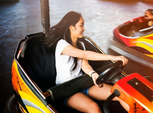 Mulher adulta nova que joga no carro abundante no parque de diversões
