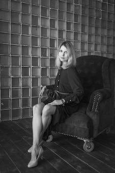 Mulher adulta nova que senta-se na cadeira. preto e branco.