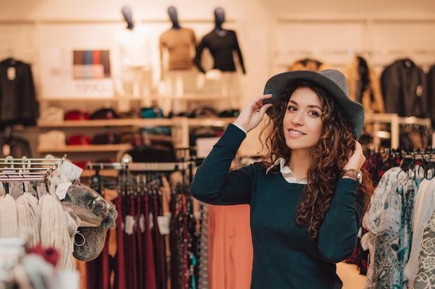 Mulher adulta nova que tenta no chapéu em uma loja.