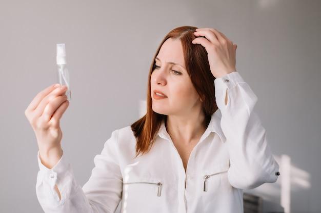 Mulher adulta, olhando e verificar o gel higieniza em casa. mulher usa um limpador de mãos antibacteriano.
