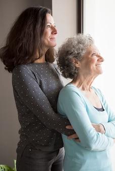 Mulher adulta pensativa, abraçando a mãe e em pé na janela