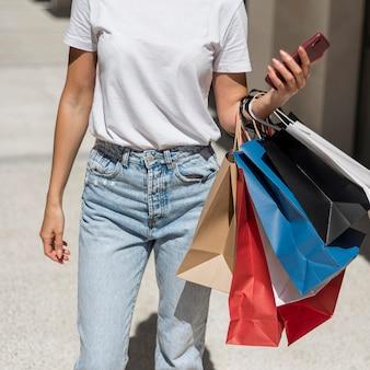Mulher adulta posando com sacolas de compras
