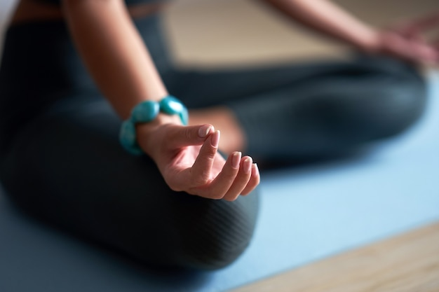 Mulher adulta praticando ioga em casa