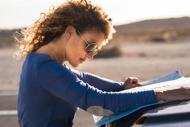 Mulher adulta procurando papel mapa de viagem rodoviária no carro do lado de fora com a paisagem ao fundo - conceito de mulheres viajando sozinhas com o veículo e desfrutando de empoderamento